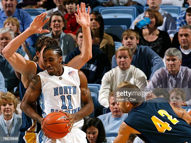 Chris Devine and James Powell of the UC Santa Barbara Gauchos defend against Quentin Thomas of the North Carolina Tar Heels during the first half at...