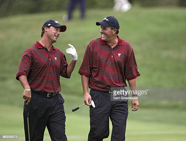 Chris DiMarco and Phil Mickelson of the US team joke around as they approach the green during the fourball matches in the third round of The...