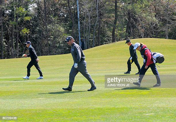 Chris DiMarco of the US and his caddy and wife Amy DiMarco walk with South Korean KJ Choi and Anthony Kim in high winds during the second round of...