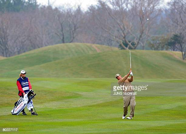 Chris DiMarco of the US hits an approach shot as his caddy and wife Amy DiMarco looks on during the first round of the Ballantine's Championship golf...