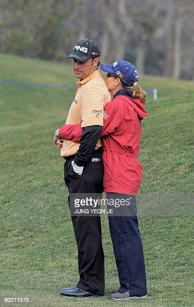 Chris DiMarco of the US is hugged by his caddy and wife Amy DiMarco during the afternoon ProAm event at the Pinx Golf Club in Jeju Island on March 12...