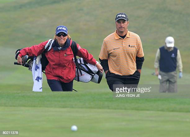 Chris DiMarco of the US walks with his caddy and wife Amy DiMarco during the afternoon ProAm event at the Pinx Golf Club in Jeju Island on March 12...