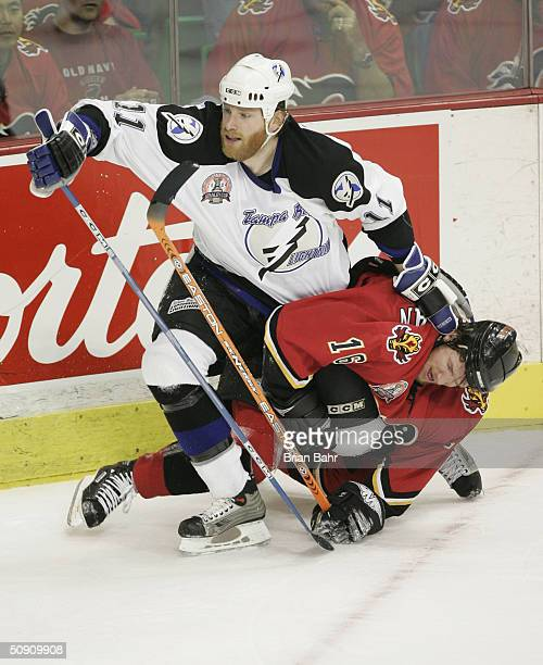 Chris Dingman of the Tampa Bay Lightning pushes away Shean Donovan of the Calgary Flames during the first period in game three of the NHL Stanley Cup...