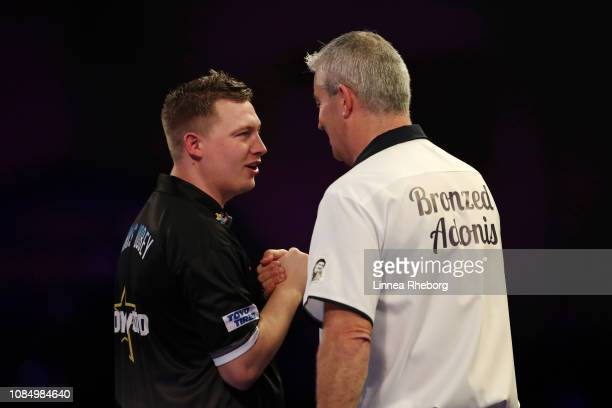 Chris Dobey of England and Steve Beaton of England shake hands after their second round match during Day Eight of the 2019 William Hill World Darts...