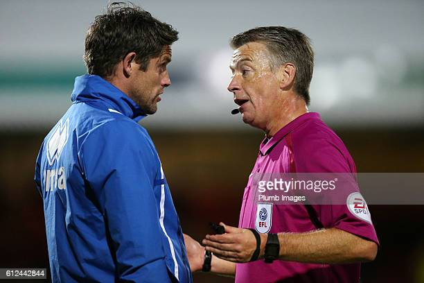 Chris Doig of Grimsby Town talks to referee Mark Haywood after James McKeown of Grimsby Town was sent off during the checkatrade Trophy match between...