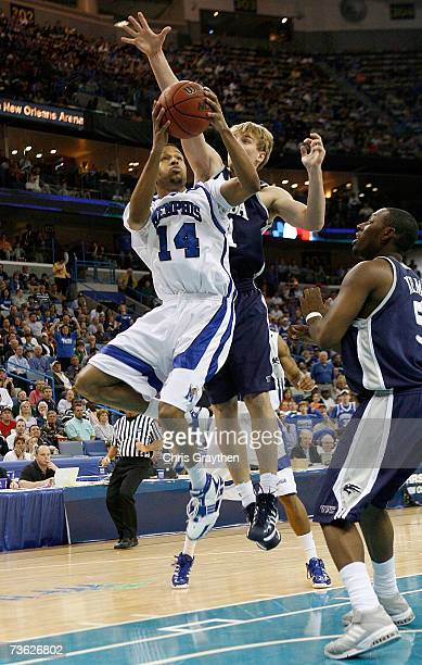 Chris Douglas-Roberts of the Memphis Tigers drives to the basket against the defense of Denis Ikovlev of the Nevada Wolf Pack during round two of the...