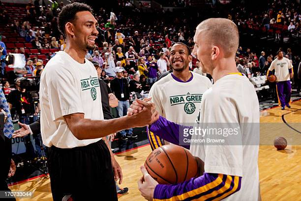 Chris Duhon and Steve Blake of the Los Angeles Lakers greet Jared Jeffries of the Portland Trail Blazers before their game during NBA Green Week on...