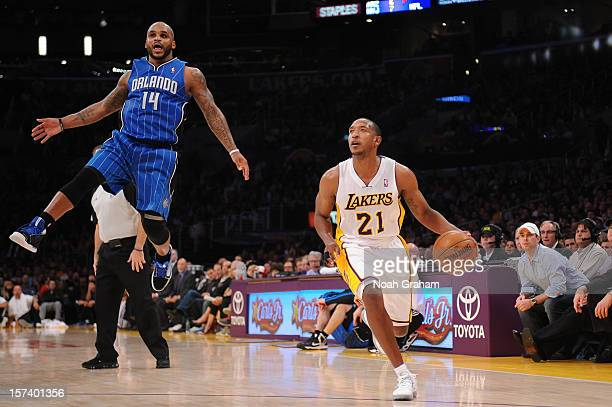 Chris Duhon of the Los Angeles Lakers dribbles against Jameer Nelson of the Orlando Magic at Staples Center on December 2 2012 in Los Angeles...