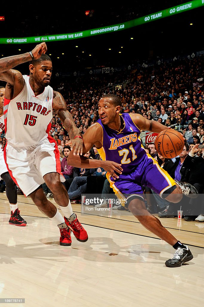 Chris Duhon #21 of the Los Angeles Lakers drives against Amir Johnson #15 of the Toronto Raptors on January 20, 2013 at the Air Canada Centre in Toronto, Ontario, Canada.