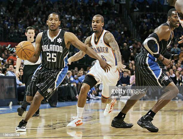 Chris Duhon of the Orlando Magic drives on Eric Maynor of the Oklahoma City Thunder during the NBA season opening game December 25 2011 at the...
