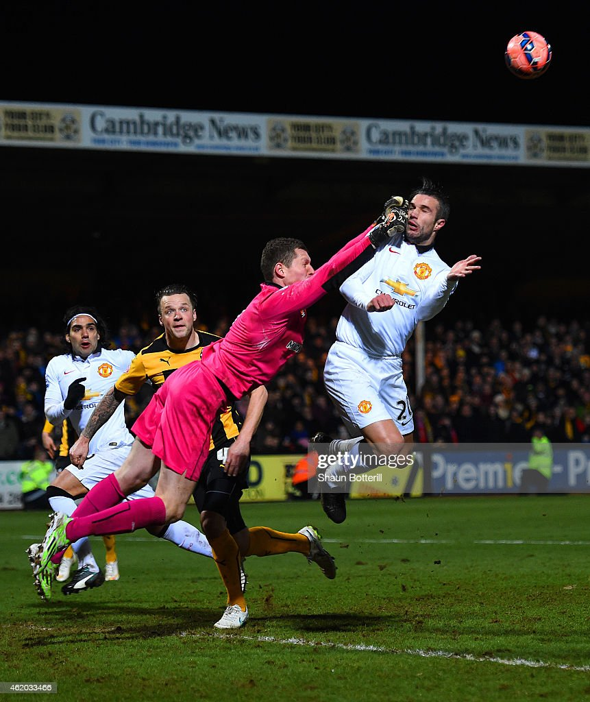 Chris Dunn of Cambridge United makes contact with Robin van Persie of Manchester United as he punches the ball clear during the FA Cup Fourth Round match between Cambridge United and Manchester United at The R Costings Abbey Stadium on January 23, 2015 in Cambridge, England.