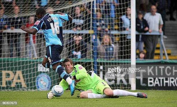 Chris Dunn of Northampton Town saves at the feet of JonPaul Pittman of Wycombe Wanderers during the Johnstone's Paint Trophy First Round Match...