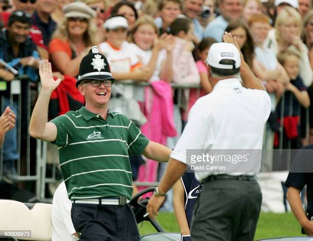 Chris Evans of England wears a policeman's hat having fun with Mark O'Meara captain of the USA team on the range before the monday fourball matches...