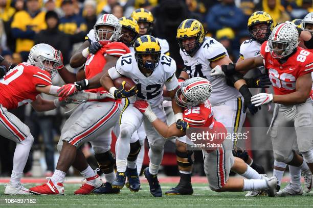 Chris Evans of the Michigan Wolverines breaks through the line as Tuf Borland of the Ohio State Buckeyes drags him down in the fourth quarter at Ohio...