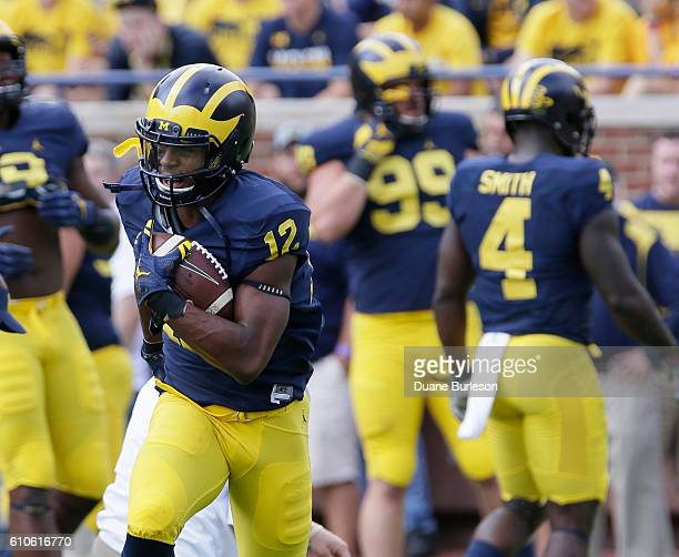 Chris Evans of the Michigan Wolverines carries the ball during warmups for a game against the Colorado Buffaloes at Michigan Stadium on September 17...