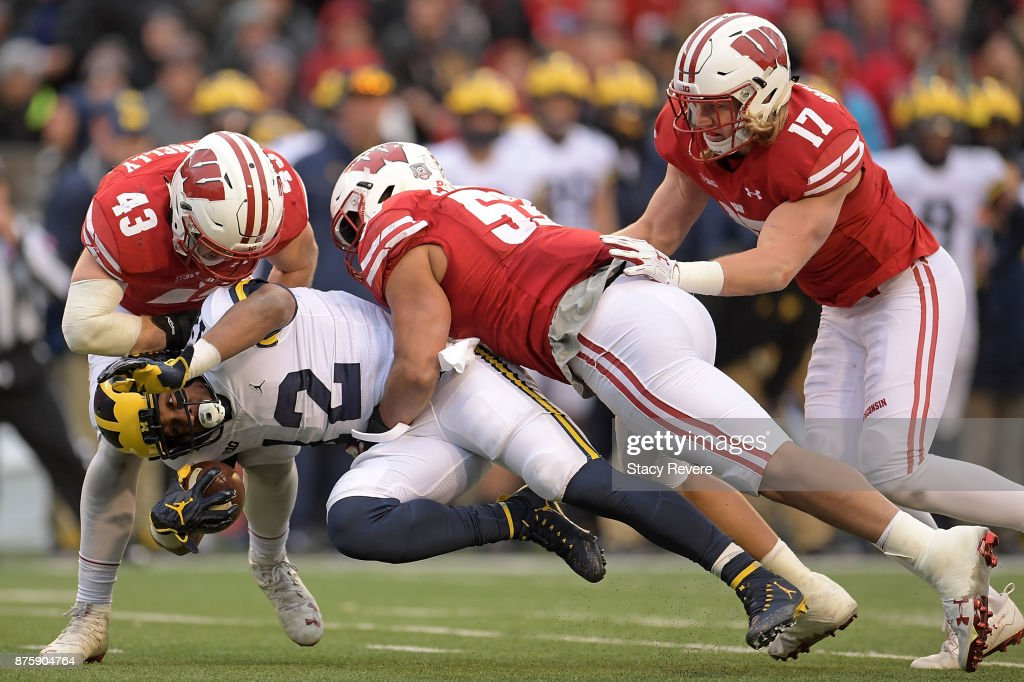 Chris Evans #12 of the Michigan Wolverines is brought down by Ryan Connelly #43 and T.J. Edwards #53 of the Wisconsin Badgers during the fourth quarter of a game at Camp Randall Stadium on November 18, 2017 in Madison, Wisconsin.
