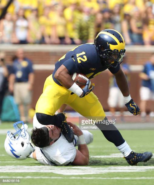 Chris Evans of the Michigan Wolverines runs for a first down as Jack Flor of the Air Force Falcons makes the stop and loses his helmet during the...