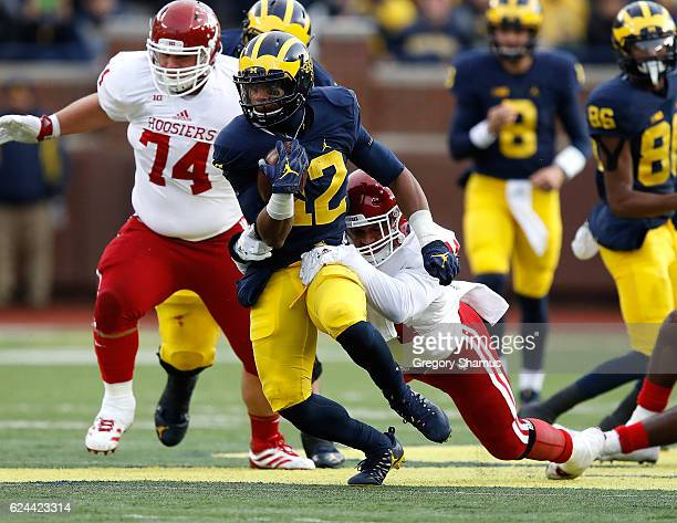 Chris Evans of the Michigan Wolverines tries to escape the tackle of Marcus Oliver of the Indiana Hoosiers during a first half run on November 19...