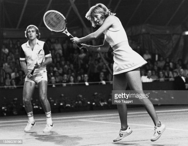 Chris Evert-Lloyd of the United States plays a double handed forehand return smash as her British partner John Lloyd looks on during the Love Doubles...