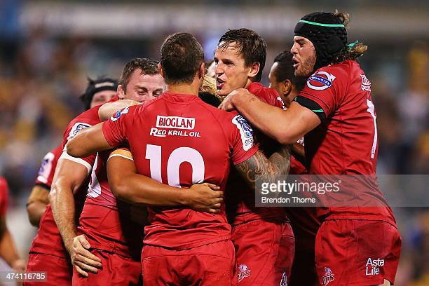 Chris FeauaiSautia of the Reds celebrates with team mates after scoring a try during the round two Super Rugby match between the Brumbies and the...