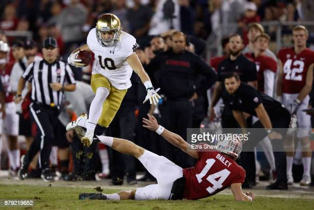 Chris Finke of the Notre Dame Fighting Irish jumps over Jake Bailey of the Stanford Cardinal on a punt return at Stanford Stadium on November 25 2017...