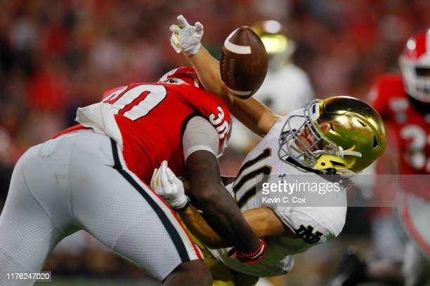Chris Finke of the Notre Dame Fighting Irish pulls in a first half catch next to Tae Crowder of the Georgia Bulldogs at Sanford Stadium on September...