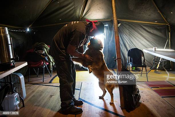 Chris Firethunder, a member of the Oglala Lakota Native American tribe, plays with his dog while living at a spiritual camp, set up by numerous...