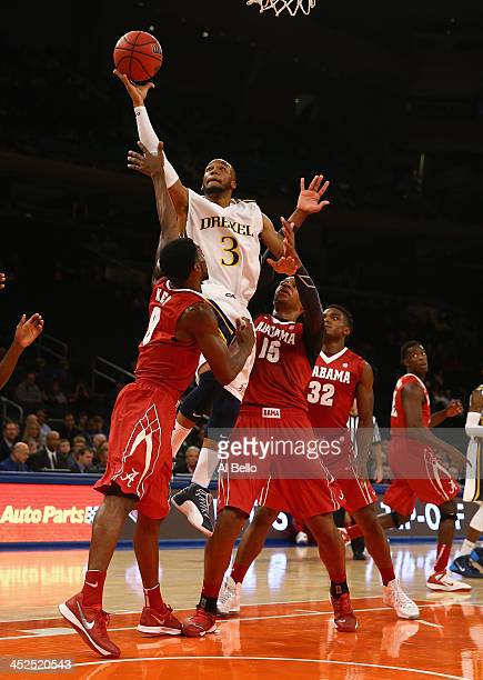 Chris Fouch of the Drexel Dragons shoots against Algie Key of Alabama Crimson Tide and Nick Jacobs of during their consolation game of the NIT Season...