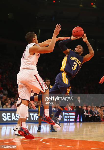 Chris Fouch of the Drexel Dragons shoots against Nick Johnson of the Arizona Wildcats during their Semi Final game of the NIT Season Tip Off at...
