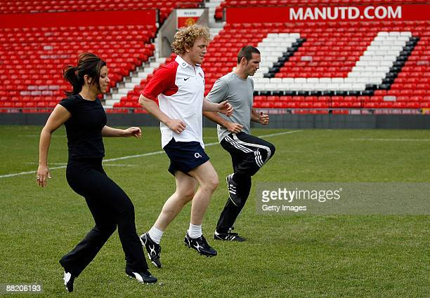 Chris Foy of the Daily Mail and Gail Davis of Sky Sports News warm up with England's Sam Vesty during a kicking clinic for media at Old Trafford on...