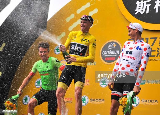 Chris Froome of Britain celebrates winning the Tour de France China Criterium as Rigoberto Uran of Colombia and France's Warren Barguil look on in...