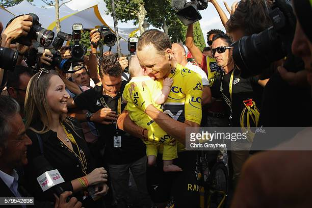 Chris Froome of Great Britain and Team Sky celebrates victory with his family as he is surrounded by media during stage twenty one of the 2016 Le...