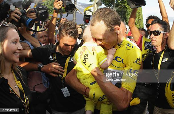 Chris Froome of Great Britain and Team Sky celebrates victoty with his family as he is surrounded by media during stage twenty one of the 2016 Le...