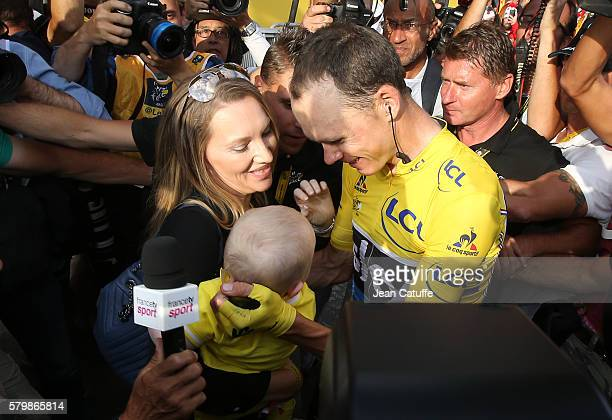 Chris Froome of Great Britain and Team Sky is congrulated at finish line by his wife Michelle Froome and their son Kellan Froome following stage 21...