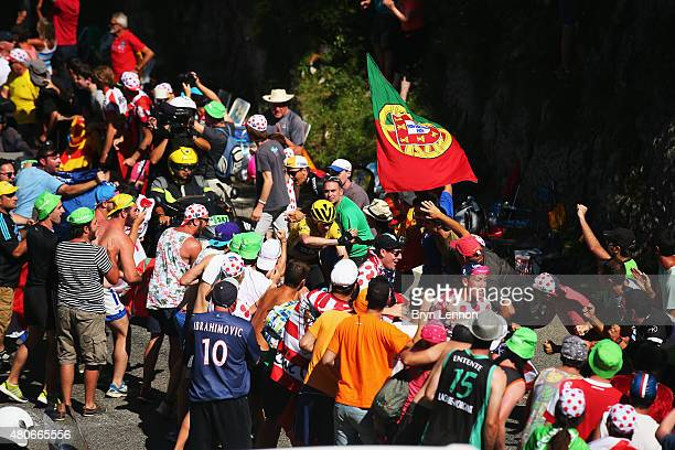Chris Froome of Great Britain and Team Sky signals to fans to move out of the way as he climbs the Col de Soudet during stage ten of the 2015 Tour de...