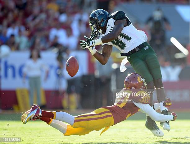 Chris Gant of the Hawaii Warriors drops a catch as he is tackled by Brian Baucham of the USC Trojans during the first quarter at Los Angeles Coliseum...