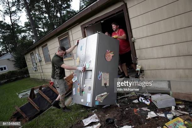 Chris Gaspard and Derek Pelt help remove a refrigerator and other ruined items from their friend Bryan Parson's home following flooding in the wake...