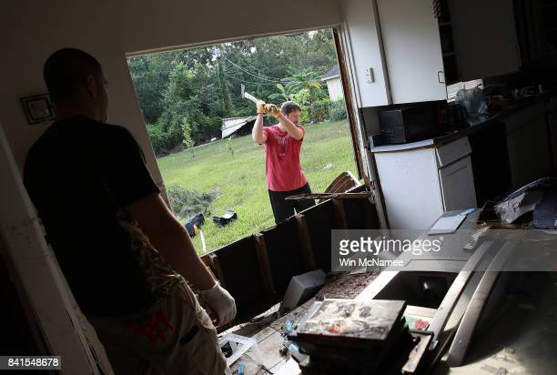 Chris Gaspard uses an axe to remove a portion of his friend Bryan Parson's home while helping to remove damage caused by flooding brought on by...