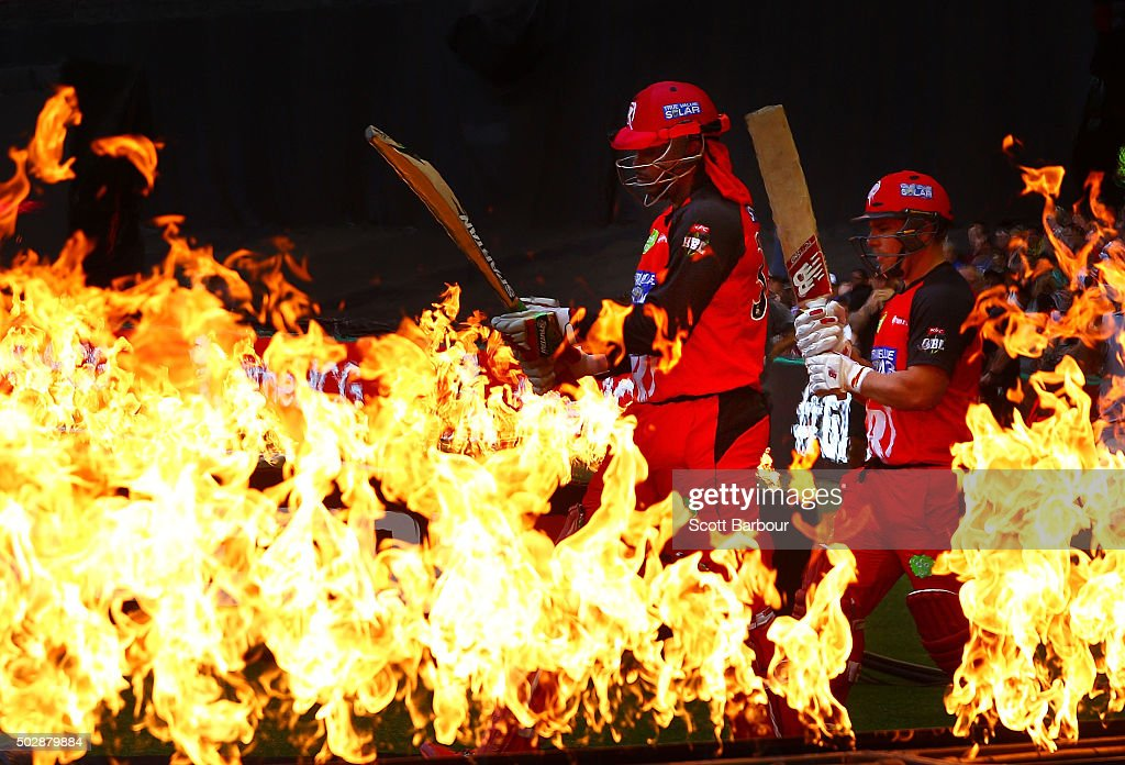 Chris Gayle and Aaron Finch of the Renegades walk through flames to open the batting during the Big Bash League match between the Melbourne Renegades and the Perth Scorchers at Etihad Stadium on December 30, 2015 in Melbourne, Australia.