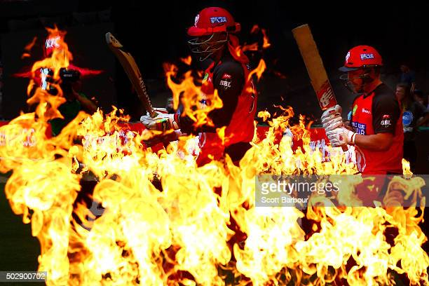 Chris Gayle and Aaron Finch of the Renegades walk through flames to open the batting during the Big Bash League match between the Melbourne Renegades...