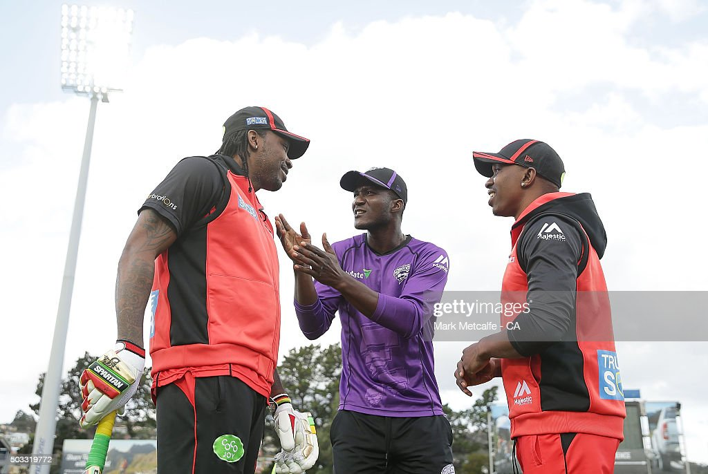 Chris Gayle and Dwayne Bravo of the Renegades and Darren Sammy of the Hurricanes talk on the field before the Big Bash League match between the Hobart Hurricanes and the Melbourne Renegades at Blundstone Arena on January 4, 2016 in Hobart, Australia.