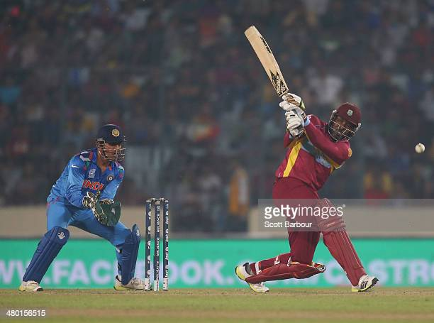 Chris Gayle of the West Indies bats as MS Dhoni of India looks on during the ICC World Twenty20 Bangladesh 2014 match between the West Indies and...