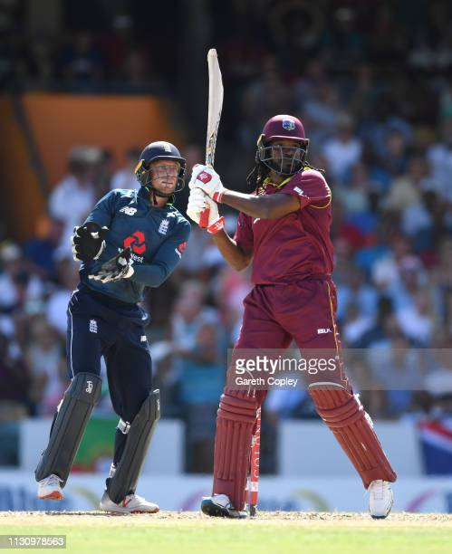 Chris Gayle of the West Indies bats watched by England wicketkeeper Jos Buttler during the 1st One Day International match between the West Indies...
