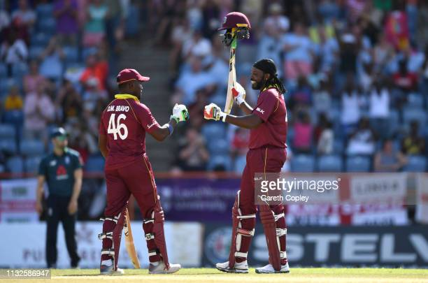 Chris Gayle of the West Indies celebrates with Darren Bravo after reaching 10000 career ODI runs during the 4th One Day International match between...