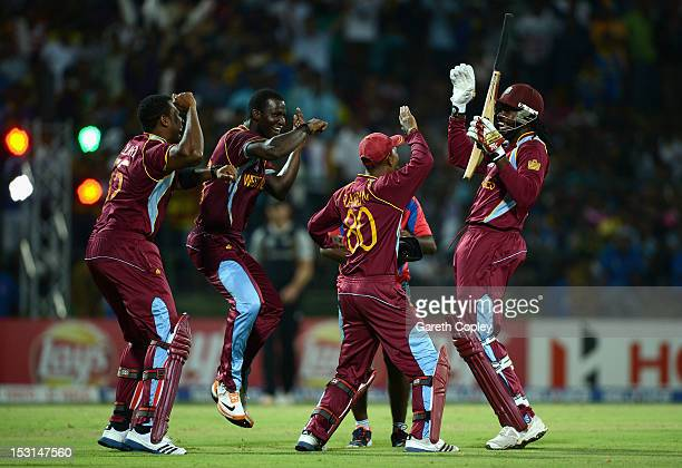 Chris Gayle of the West Indies celebrates with Kieron Pollard Darren Sammy and Danesh Ramdin after winning the superover to win the ICC World...