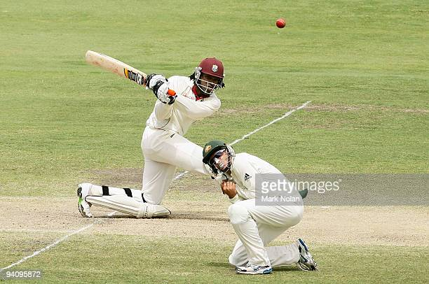 Chris Gayle of the West Indies hits out as Michael Hussey of Australia takes cover during day four of the Seond Test match between Australia and the...