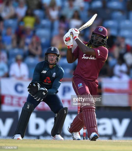Chris Gayle of the West Indies hits out for six runs watched by England wicketkeeper Jos Buttler during the 4th One Day International match between...