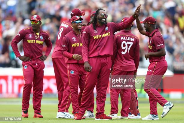 Chris Gayle of West Indies celebrates with Kemar Roach after taking the wicket of Ross Taylor of New Zealand during the Group Stage match of the ICC...
