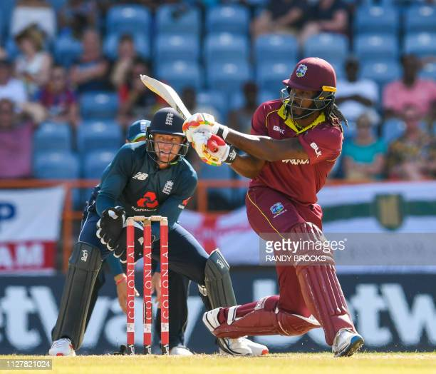 Chris Gayle of West Indies hits 4 as Jos Buttler of England watches during the 4th ODI between West Indies and England at Grenada National Cricket...