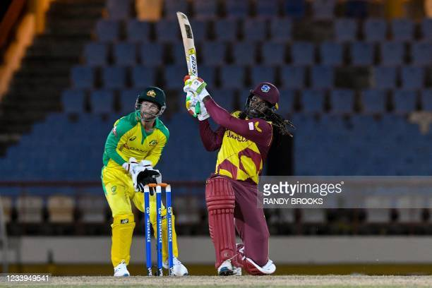 Chris Gayle of West Indies hits 6 as Matthew Wade of Australia watches during the 3rd T20I between Australia and West Indies at Darren Sammy Cricket...